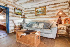 Rustic cabin with exposed log beam walls, wood floors, light blue leather sofa with trunk styled coffee table