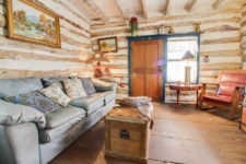 Rustic cabin with wood floors, light blue leather sofa, red leather and wood chair and wood trunk styled coffee table