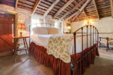 Rustic room with vaulted exposed beam ceiling, stone walls and floor, and large bed flanked by nightstands with lamps