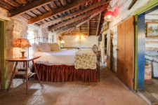 Rustic room with vaulted beamed ceiling, ivory stone walls, stone floors and large bed with red skirt and floral quilt