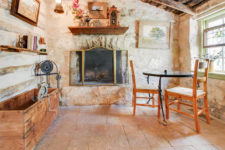 Room with ivory stone walls, vaulted ceiling, stone floors, fireplace and small round table with two wood and wicker chairs