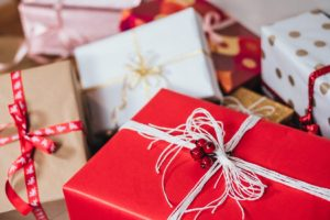 pile of red white and kraft paper wrapped packages tied with ribbons