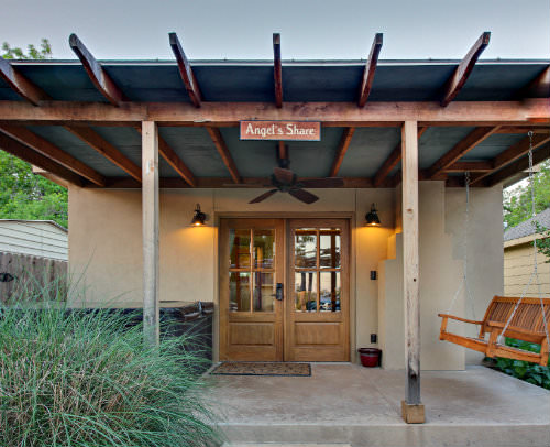 Outdoor view of beige stucco cabin, exposed beam covered porch, hot tub, hanging swing, double doors and ornamental grass