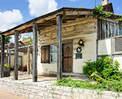 Outdoor view of rustic log cabin with exposed beam covered porch, stone terrace and blue skies