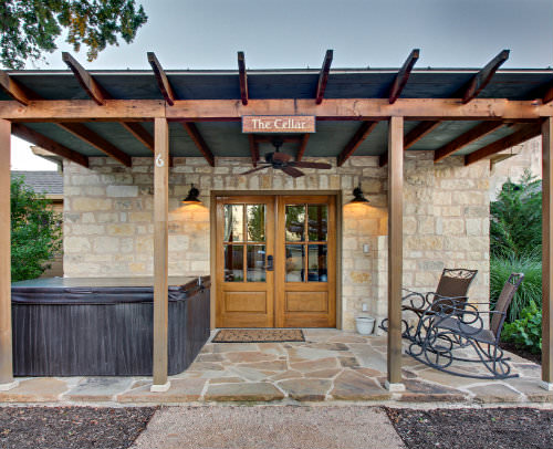 Outdoor view of stone cabin with exposed beam covered porch with stone slab, hot tub and two rocking chairs