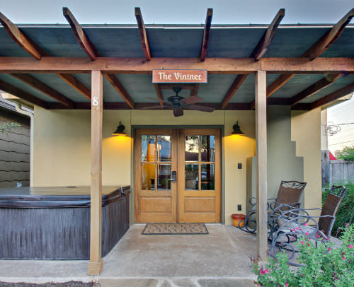 Outdoor view of beige stucco cabin, exposed beam covered porch, wood and glass double doors, rocking chairs and hot tub