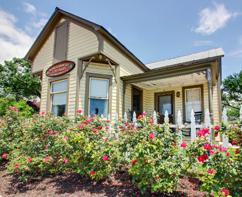 Outdoor view of tan cabin with brown trim, lots of windows, surrounded by flowering shrubs and blue skies