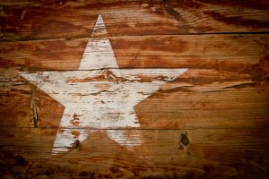 white star painted on rough brown wood horizontal boards