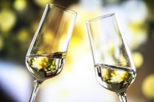two flutes with white wine meeting being used to toast