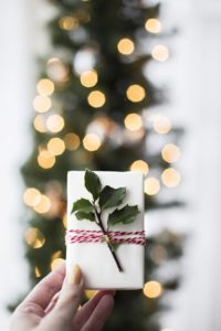 white gift box with evergreen sprig and red bow held against out of focus christmas treeheld-up-against-blurred-christmas-tree-