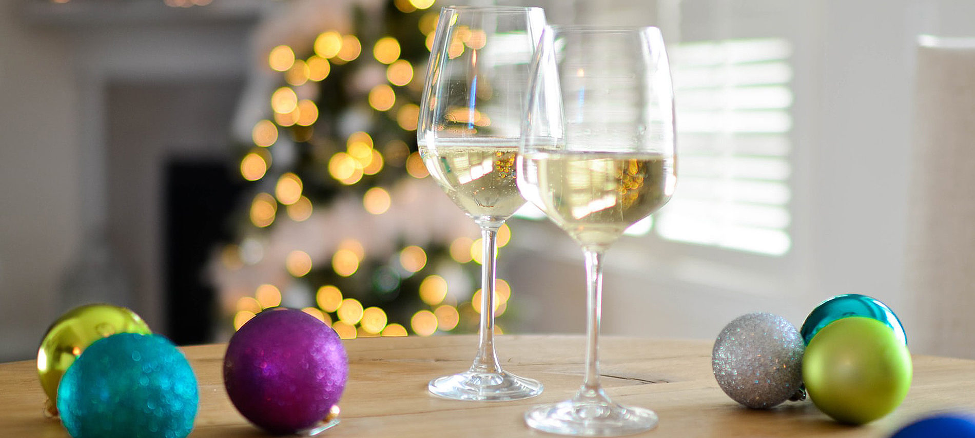 purple blue green christmas balls on table with two glasses of white wine christmas tree with white lights out of focus in background
